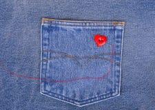 Il cuore rosso ha modellato il bottone con l'ago ed il filo rosso sul fabr del denim fotografia stock