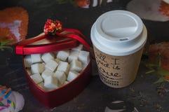 Il cuore rosso ha modellato la scatola con una tazza di caffè immagine stock