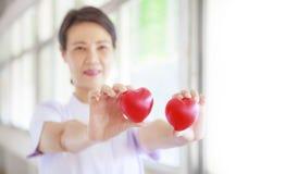 Il cuore rosso ha tenuto dalla mano femminile sorridente del ` s dell'infermiere, rappresentante dando la mente di servizio di al immagini stock