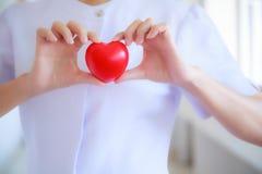 Il cuore rosso ha tenuto dalla mano femminile sorridente del ` s dell'infermiere, rappresentante dando la mente di servizio di al fotografie stock