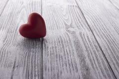 Il cuore rosso sul bianco ha dipinto il fondo di legno Fotografie Stock Libere da Diritti