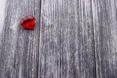 Il cuore rosso sul gray ha dipinto il fondo di legno Immagine Stock Libera da Diritti