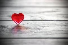 Il cuore rosso sul gray ha dipinto il fondo di legno Fotografia Stock