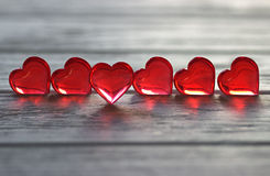 Il cuore rosso trasparente sul gray ha dipinto il fondo di legno Fotografia Stock Libera da Diritti