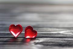 Il cuore rosso trasparente sul gray ha dipinto il fondo di legno Fotografie Stock