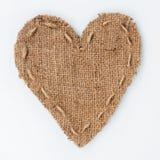 Il cuore simbolico di tela da imballaggio si trova su un fondo bianco Fotografia Stock Libera da Diritti