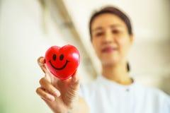 Il cuore sorridente rosso ha tenuto dalla mano femminile sorridente del ` s dell'infermiere, rappresentante dando la mente di ser immagini stock