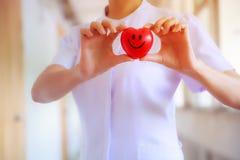 Il cuore sorridente rosso ha tenuto dalla mano femminile del ` s dell'infermiere, rappresentante dando la mente di servizio di al immagini stock