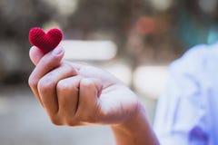 Il cuore tricotta nelle mani della ragazza immagini stock