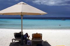 Il Curacao - distendendosi sotto un ombrello di spiaggia Fotografia Stock Libera da Diritti