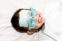 Il cuscinetto di raffreddamento del gel dell'attaccatura del bambino sulla sua fronte Immagini Stock Libere da Diritti