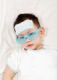 Il cuscinetto di raffreddamento del gel dell'attaccatura del bambino sulla sua fronte Fotografia Stock