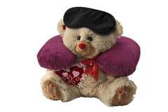 Il cuscino per il collo e la maschera per l'occhio sono messi su un orso del giocattolo Accessori di sonno per viaggiare Isolato  Immagine Stock Libera da Diritti