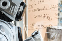 Il cyborg astuto sta stando con l'indicatore contro il bordo trasparente Immagine Stock
