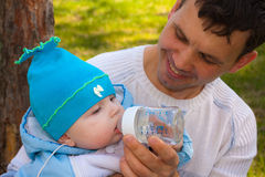 Il daddy concede bere da una bottiglia al figlio Fotografia Stock