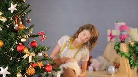 Il dancing allegro del bambino con i cervi della peluche si avvicina all'albero di Natale di illuminazione, felicità video d archivio