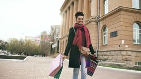 Il dancing attraente della ragazza della corsa mista e si diverte mentre cammina giù la via con le borse Giovane donna felice che fotografie stock libere da diritti