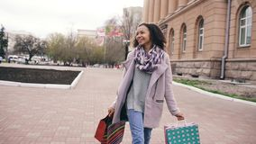 Il dancing attraente della ragazza della corsa mista e si diverte mentre cammina giù la via con le borse Giovane donna felice che fotografia stock libera da diritti