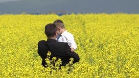 Il dancing dell'uomo d'affari con il bambino elegante nel campo della violenza del fiore, divide la gioia stock footage