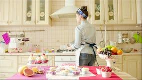 Il dancing della ragazza con l'utilità sbatte nella cucina