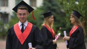 Il dancing e la rappresentazione laureati divertenti a lungo hanno preveduto il diploma per la macchina fotografica, felicità stock footage