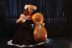 Il dancing ed il canto hawaiani femminili sorridenti della ragazza con gli strumenti musicali gradiscono le ukulele Fotografia Stock