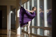 Il dancing grazioso della ballerina in una gamba porpora del vestito ha sollevato il livello, st Fotografie Stock