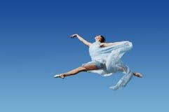 Il danzatore che salta contro la SK blu fotografia stock libera da diritti