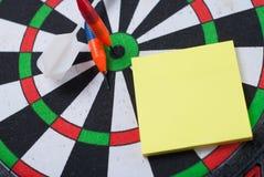Il dardo ha colpito il centro dell'obiettivo ed attacca l'autoadesivo, fotografia stock