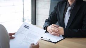 Il datore di lavoro che arriva per un'intervista di lavoro, uomo d'affari ascolta le risposte del candidato che spiega circa il s fotografia stock