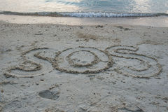 """Il """" del """" SOS di parola scrive in sabbia sulla spiaggia Fotografia Stock Libera da Diritti"""