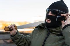 Il delinquente mascherato sta negoziando su un telefono cellulare immagini stock libere da diritti