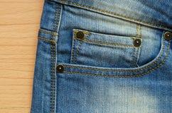 Il denim blu con la cucitura, i perni ed i jeans intascano su legno Immagine Stock