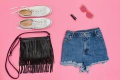 Il denim mette, scarpe da tennis bianche, borsa nera Backgro rosa luminoso Fotografie Stock