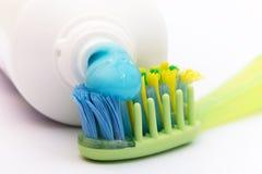 Il dentifricio in pasta blu su uno spazzolino da denti colorato Immagini Stock Libere da Diritti