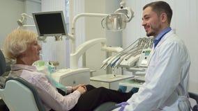 Il dentista accoglie il cliente femminile al suo ufficio immagine stock libera da diritti