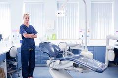 Il dentista in blu sfrega la condizione con i braccioli attraversati accanto alla sedia immagini stock