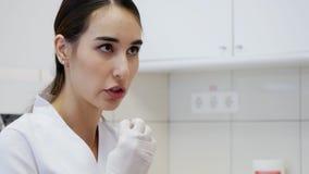 Il dentista della donna dice al paziente come pulire i vostri denti Chiamata al dentista stock footage