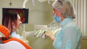 Il dentista dice il paziente circa gli strumenti quale tratterà i suoi denti archivi video
