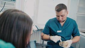 Il dentista dice il paziente circa i denti del giudizio Dentista maschio stock footage