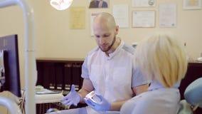Il dentista dice il paziente circa il trattamento dei denti stock footage