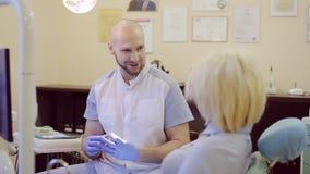 Il dentista dice il paziente circa il trattamento dei denti video d archivio