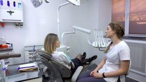 Il dentista discute il trattamento dentario con il paziente stock footage