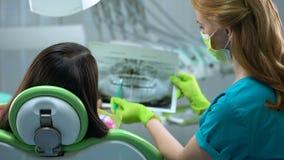 Il dentista ed i denti di sorveglianza pazienti fanno i raggi x dell'immagine, cavità, malattia periodentale archivi video