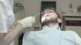 Il dentista esamina il paziente nell'ufficio archivi video