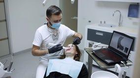 Il dentista esplora i denti pazienti del ` s con un analizzatore 3d stock footage