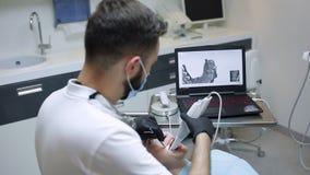 Il dentista esplora i denti pazienti del ` s con un analizzatore 3d archivi video