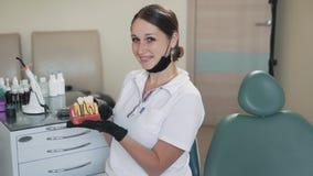 Il dentista grazioso della donna sorride alla macchina fotografica e tiene il modello dei denti in sue mani, movimento lento video d archivio