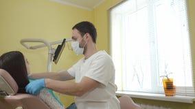 Il dentista maschio prepara esaminare un paziente femminile nella clinica dentaria, mette sopra il panno sterile del petto stock footage