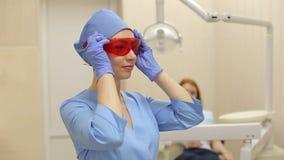 Il dentista mette sui vetri arancio protettivi prima del lavoro con il cliente stock footage